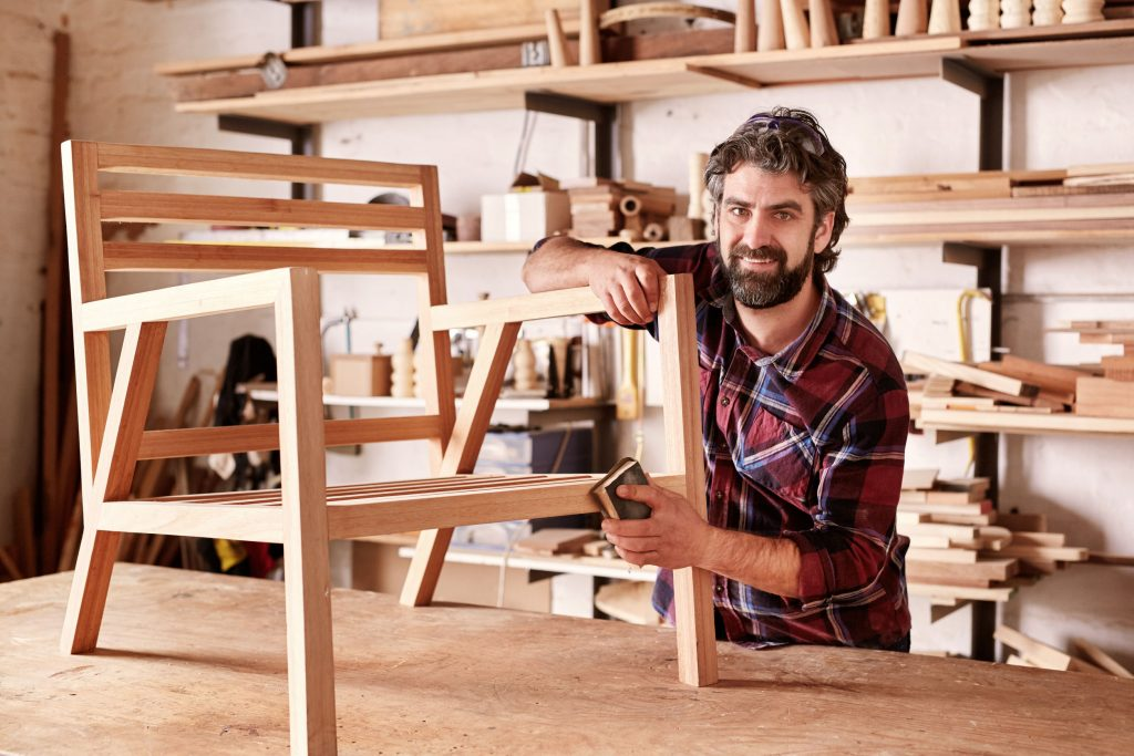 54601248 - portrait of an artisan designer, with new piece of furniture, finishing off the sanding of the chair in his studio, with shelves of wood behind him