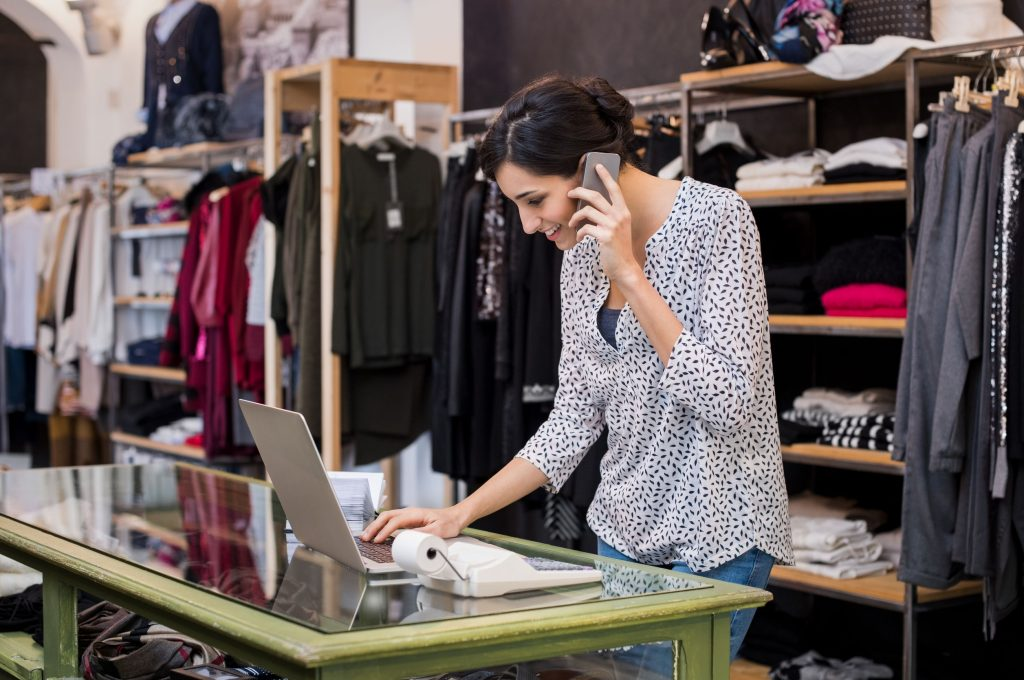 69226668 - young businesswoman talking over phone while checking laptop in her clothing store. young entrepreneur in casual using laptop and talking on mobile. store manager woman checking important documents on laptop. small business concept.